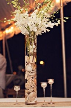 Are you thinking about having your wedding by the beach? Are you wondering the best beach wedding flowers to celebrate your union? Here are some of the best ideas for beach wedding flowers you should consider. Beach Wedding Centerpieces, Reception Decorations, Wedding Table, Table Decorations, Centerpiece Ideas, Tall Centerpiece, Seashell Centerpieces, Simple Centerpieces, Wedding Lanterns