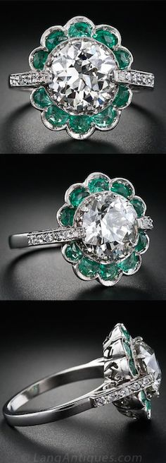 *2.56 Carat Vintage Diamond Ring with Emeralds, A big, bright and beautiful European-cut diamond weighing 2.56 carats (but which looks even larger in its platinum setting) glistens and glows from this extraordinary Art Deco mounting. The diamond is enveloped in a blossoming flower motif with ten half-moon shape emeralds serving as petals. In addition to eight tiny prongs, the diamond is embraced by two diamond-set shoulders which rise up from the ring shank.