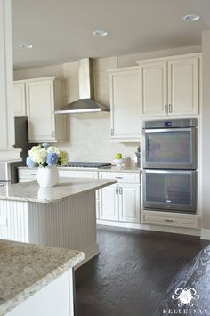 Kelley Nan: One Room Spring Tour: Spring Styled Kitchen and Baby Blue Salad Recipe | Spring  white kitchen with dark hardwood floors, stainless steel vent hood, and blue and white hydrangeas