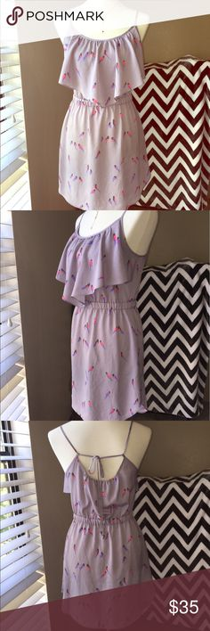 AEO flounce dress This cute grey AEO dress has a flattering flounce top and a gathered waist. A rounded hemline compliments any pair of legs, while a tie back detail gives the dress some flair. The dress is grey adorned with pink and purple patterned birds. American Eagle Outfitters Dresses
