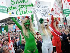 Ukrainian Femen protestors hold signs during a demonstration in Rome that protested Berlusconi's sex scandal