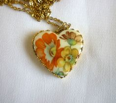 Vintage pendant necklace featuring a porcelain floral heart on a gold tone cable chain. The porcelain heart has a hand painted white background and highlights red, yellow and purple flowers and sits in a gold tone setting. It is in great vintage condition with very light surface scratches on backside. This vintage necklace is marked Korea on the chain closure.    Measurements:    Pendant – 2.5 cm (1 inch)    Chain – 46 cm (18 inches)    Condition: Very good vintage condition.