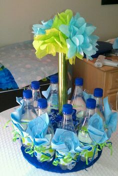 Center piece for baby shower.Bottled water,napkin and utensils.Tissue flowers glued in a wrapping paper roll cut in half and wrapped with the paper.