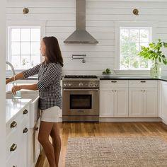 Sabbbe Interior Design: Hardi plank siding backsplash behind stove; cabinet pulls, black/white/brass/wood/plants/glass.