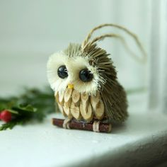 Handmade from natural fibers, twigs, and seeds, this forest bird peeps out from between the branches of a Christmas tree with all-knowing eyes.