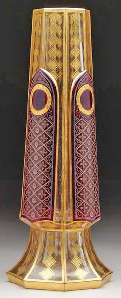 A Moser cut overlay decorated vase, clear to ruby in tapered octagon form having extensive gold decoration with cathedral panels of cranberry with intricate cut decoration. Czechoslovakia, circa 1893-1930