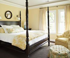 Dark wood, yellow bedroom, w/ white and blue accent pillows