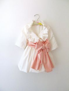 Ivory pleated jacket with pink stripe sash