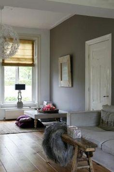 Naast grijze muur en grijze bank een bruine vloer en wit meubilair ...