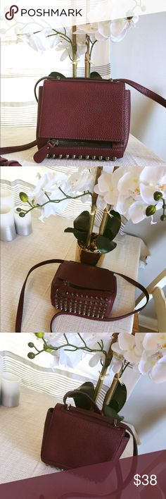 Burgundy studded mini satchel cross body Resembles an Alexander wang Rocco bag but it is NOT a replica. Boutique brand. it's so cute and sturdy, perfect for carrying the necessities. Button closure on the outside. Bottom zip extra pocket. Zip inner pocket and open pocket on inside. In like new condition. Bags Crossbody Bags