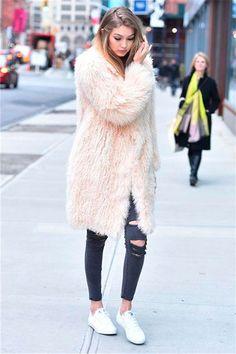 Street style look Gigi Hadid usando maxi casaco Fluffy Coat rosé, calça jeans preta rasgada e tênis branco.
