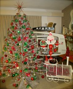 Christmas vignette of 60's red and green pom-pom aluminum tree, vintage train birdcage, Santa store display, and a 1950's Argus display filled with xmas smalls