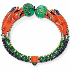 Coral and Emerald Dragon-Head Bracelet, Cartier, Paris, 1928 Designed by Charles Jacqueau, enamelled gold, carved coral heads set with sapphire horns and diamond eyes and teeth, holding two melon-cut emerald beads of 48.43 carats with onyx tips
