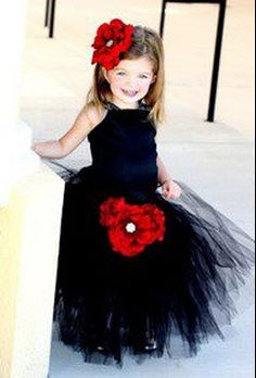 Adorable flower girl in black tulle dress with red flower headband.
