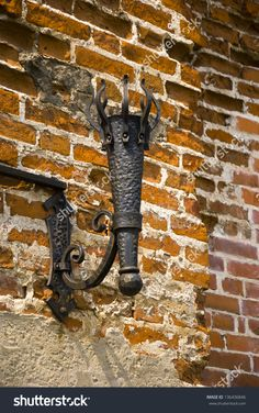 Iron Stand for torches hanging on the brick wall of a medieval fortress by Igor Rozhkov, via ShutterStock Outdoor Torches, Fire Torch, Medieval Fortress, Pond Design, Forging Metal, Rustic Lighting, Wall Lighting, Iron Work, Street Lamp