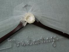 Handmade Ivory Silk and Organza Flower Bridal Hanger! This is a walnut stained wood hanger with a hand made flower with a flower having 6 layers of