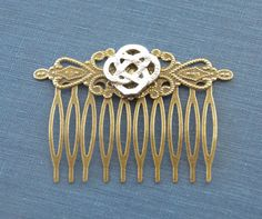 This beautiful bridal hair comb was handmade with love using a silver-plated Celtic knot atop an antiqued, filigree detailed hair comb.