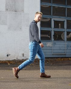 Mens fashion street style outfit. 90's style vintage blue high waisted light blue denim jeans with a navy and white striped jumper, brown leather high top boots with transparent glasses for men.