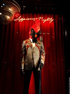 Bergdorf Goodman's Window Display, A CLOSED WINDOW DISPLAY, RED, A MANIKANE , BIRD HEAD , HUMAN BODY, FEATHERS, NIGHTTIME, DARK LIGHTING, JAZZY, DISCO BALL