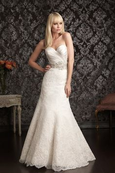 Allure Bridals Style No. 9004. Elegant and sophisticated. This slim gown combines lace and satin beautifully. The natural waist bodice features a sweetheart neckline and asymmetrical ruching. Swarovski crystals and beading create a sparkling belt detail while lace finishes the gown throughout the skirt.