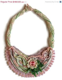 This Shibori Ribbon necklace is done in the graceful Victorian style. At the center us a hand beaded flower with leaves and with pink pearls