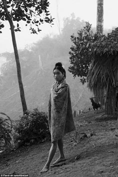 In the forest: A girl in the Palawan society stops for a portrait. In the Palawan society in China sharing and helping others is a key component to the culture