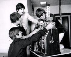 """The Beatles playing slots at the Sahara Hotel/Casino during the Las Vegas stop of the 1964 tour. According to Ivor Davis, author of """"The Beatles and Me on Tour"""", the slots had to be brought to the Beatles' suite. He says that during the photo shoot """"John kept muttering 'gambling is EVIL', like a kind of preacher."""""""