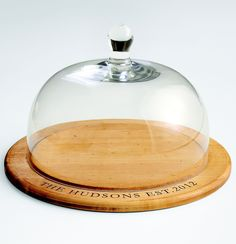 Give the happy couple a glass dome server that will become a mainstay at all their parties. The made-in-the-USA maple wood tray is perfect for housing fruit, cheese, or homemade treats. $90, $8 for personalization; redenvelope.com  - GoodHousekeeping.com