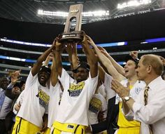 Michigan celebrates with the trophy after their 79-59  win over Florida  in the NCAA Tournament South Regional Final in Arlington, Texas.