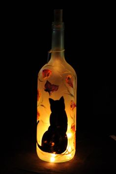 A great gift for cat lovers! A tall sitting cat in black silhouette sit serenely in a beautiful garden it stares up at a purple butterfly that hovers above.  While beautiful when unlit, when plugged in this bottle takes on a whole new look and transforms into a beautiful nightlight. Add a