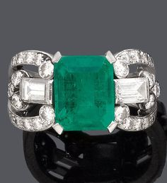 AN ART DECO EMERALD AND DIAMOND RING, CIRCA 1930. Set with 1 octagonal Colombian…