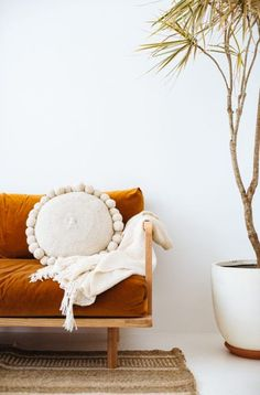 Bohemian style round pompom cushion on velvet couch