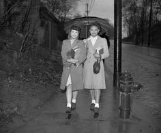 Christine Bradshaw and Estelle Joiner walking together underneath umbrella on sidewalk on their way to school, 1946. By Teenie Harris.