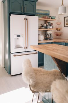 2019 kitchen design trends, warm hardware finishes and bold cabinetry colors in blue feauturing Cafe Appliances in Matte White with Brushed Bronze Hardware.