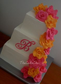 Summer Wedding - Orange and Pink Wedding. Iced in Italian meringue buttercream. Vanilla cake with vanilla bean filling, Chocolate cake with oreo cream filling and Strawberry cake with whipped strawberry filling. Gumpaste roses and monogram. I only ended up using about 1/2 of the roses I made, live and learn. ;)