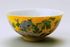 """Bol impérial - Issu de la collection Grandidier du musée Guimet, datant de 1720 (règne de Kangxi), ce bol constitue un travail d'orfèvre ciseleur avec son fond jaune - couleur de la dynastie Qing -, ses émaux collés les uns après les autres, son décor floral naturaliste. Fabriqué à Pékin dans les ateliers impériaux, il était destiné à la cour. Sa marque, inscrite en émail bleu, indique : """"Fait par commande impériale de l'empereur Kangxi"""". Par Jacqueline Saint-Medar     © Thomas/Musée Guimet…"""