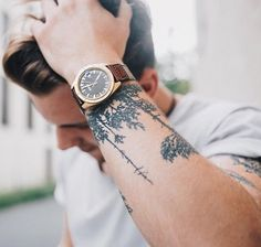 White tee. Simple watch. Arm tattoo.