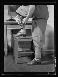 Safe clothes for women war workers. A closeup of Eunice's new uniform reveals one of its most important safety factors: the tight-buttoning trouser ankles which prelude the possibility of a loose trouser's catching in moving machinery. Note also the sturdily built, comfortable safety shoes, with box toe which helps protect the wearer from falling objects. Bendix Aviation Plant, Brooklyn, New York Photographer Ann Rosener Created March 1943