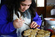 Haciendo orificios y rellenando los cupcakes de vainilla con betún de queso crema.