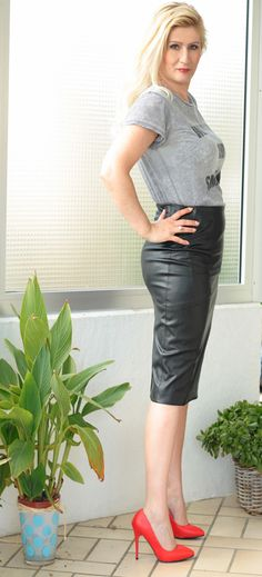 Blonde in black leather skirt tee shirt and red heels
