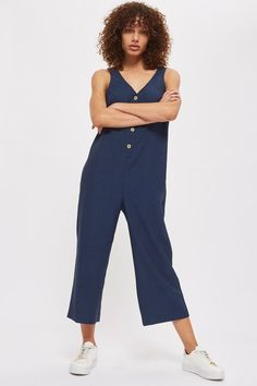 The ultimate off-duty piece, this button-up jumpsuit is our new wardrobe staple for this season. In a versatile navy blue, it comes in a slouchy shape with v-neck detailing and cropped legs.