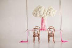 hanging floral centerpiece installation. white hydrangea with ombre pink streamers. bows and arrows.