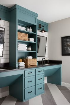For continuity, we painted the vanity the same blue tone as the lockers. We also brought in the same striped tile, but chose to install it diagonally to change things up. Black countertops, hardware, and fixtures provided the classic, masculine details that finished off the space.