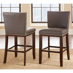 Introduce contemporary style to your dining area with the Tisbury counter height stools. Finished in a rich espresso cherry, these chairs boast solid wood legs and bonded leather seats with decorative nail head trim.