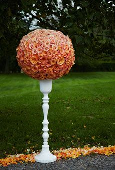 """Flank your front door, line the aisle, or bookend your driveway with glossy white pedestals topped with orange flower globes. We took a floral foam ball and inserted """"Miracle,"""" """"Milva,"""" and """"Miss Piggy"""" roses, from lightest to darkest shades, to create an ombré effect."""