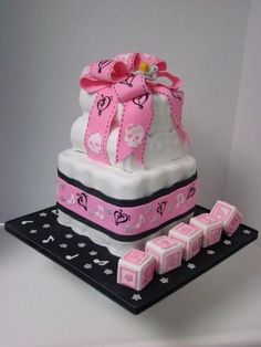 This a cake made to look like a diaper cake. It has a roll and theme with artistic music notes, and girly skulls. The blocks are made rice cereal treats and marshmallow fondant.