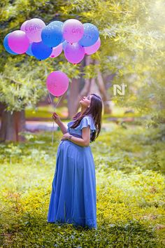 Gorgeous mom-to-be with balloons in her hand in the garden. Creative maternity p. - Gorgeous mom-to-be with balloons in her hand in the garden. Creative maternity portraits for the go -