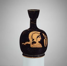 An ancient Greek terracotta lekythos/wine flask decorated with a bust of the goddess Athena, pataron of Athens, and an olive sprig (her attribute, a symbol of Athens and an appropriate adornment for a flask holding olive oil). (Metropolitan Museum of Art)