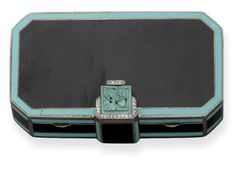 AN ART DECO ENAMEL VANITY CASE. circa 1925 -- The rectangular-shaped black enamel vanity case with turquoise-coloured enamel borders and carved turquoise and rose-cut diamond clasp opening to reveal a mirror, two powder compartments and a lipstick holder
