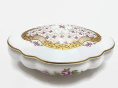 A vintage Limoges porcelain trinket box or bonbonniere with pink roses and gilt accents on a white background.  Marked Limoges, France, Porcelaine